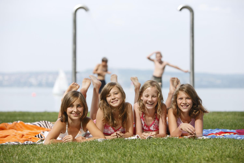 Jugendliche auf der Wiese vor dem See
