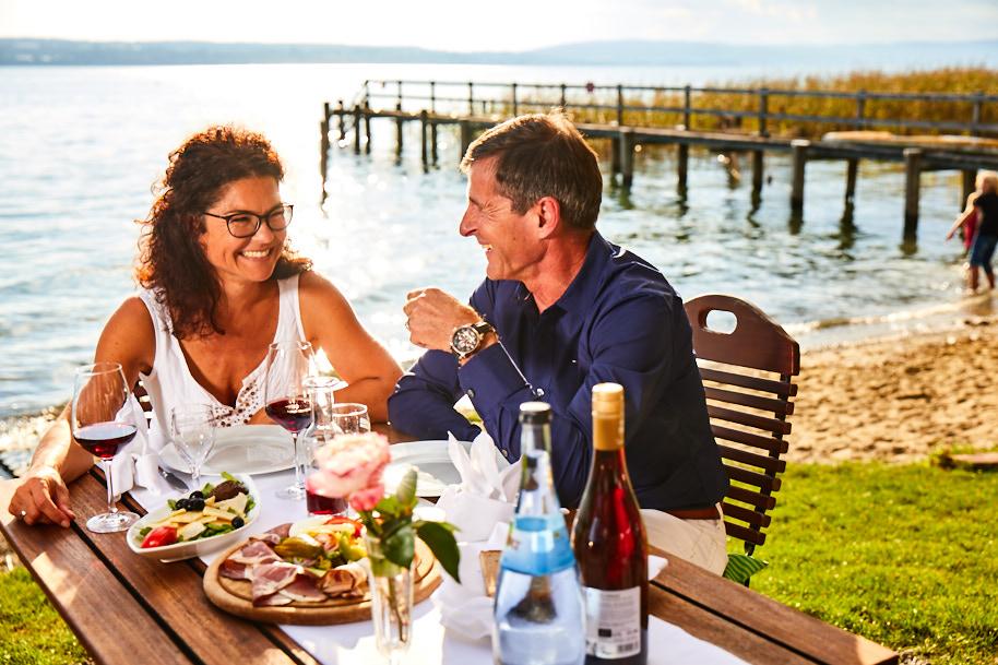 ein Paar, das direkt am Seeufer einen wohlgedeckten Tisch genießt