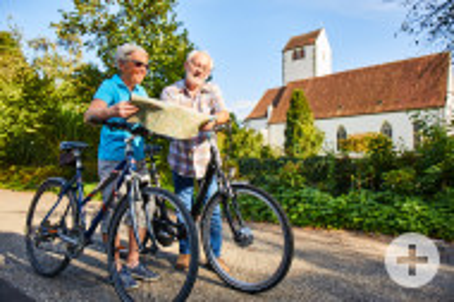 älteres Paar mit Fahrrädern, das eine Landkarte studiert